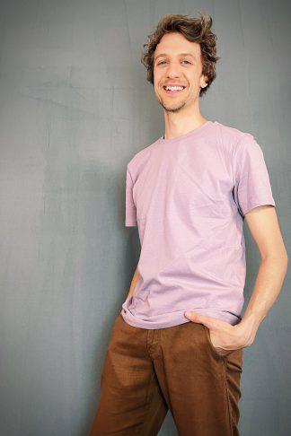Natürlicher fröhlicher Kerl trägt ein gerade geschnittenes unisex T-shirt in einem pastellfarbenen lila Farbton.