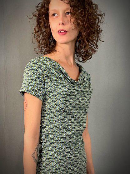 Knielanges Biojersey-Cocktailkleid mit Geometrieprint getragen von einer sympathischen Frau mit lockigen braunen Haaren