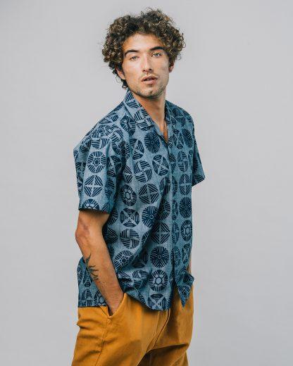 Natürlicher typ mit dunklen Locken trägt ein locker geschnittenes surferstyle Hemd in Jeansblau mit dunkelblauen Shibory style Kreisen. Der Kragen ist als v ausschnitt gestaltet. der schnitt fällt eher locker. dazu trägt er eine senffarbene Stoffhose.