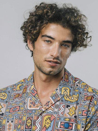 Mann Trägt leichtes Sommerhemd mit Ndebele Kunst Pint und legerem Cubano Kragen.
